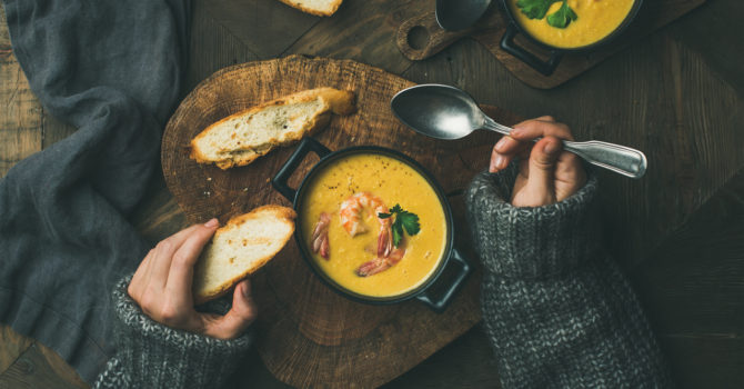 Woman In A Sweater Eating Soup